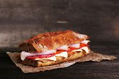Fresh and tasty sandwich with ham and cheese on paper on wooden background