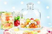 Multicolor candies in glass jars on colorful background