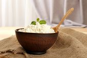 Cottage cheese in bowl with spoon on table on fabric background