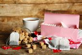 Heart shaped teabag tags and Cup of tea with on wooden background