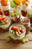 Healthy layered desserts with muesli and fruits on table