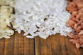 Different types of rice on wooden background