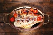 Dish of Pangasius fillet with spices and vegetables in metal tray on wooden table background