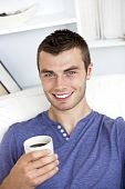 Charming Caucasian Man Holding A Cup Of Coffee Smiling At The Camera