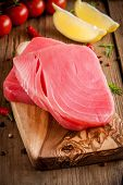 stock photo of flank steak  - Raw tuna fillet with dill lemon and cherry tomatoes in olive cutting board - JPG
