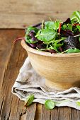 mix salad (arugula, iceberg, red beet) in a wooden bowl