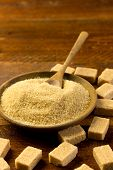 pic of sugar  - brown sugar in a wooden bowl with sugar cubes - JPG