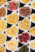 Dried pasta food selection close up in heart shaped porcelain bowls .