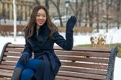 Asian girl in blue coat on the bench raised in greeting hand