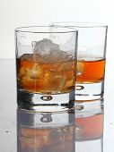 Two Glasses With Whisky And Ice On A White Background