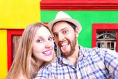 Beautiful Couple taking a selfie photo in a colorful background