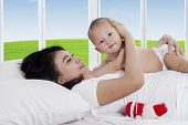 Asian Mother With Baby In Bedroom