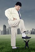 stock photo of big-foot  - Big businessman stepping his foot to tread his rival shot outdoors - JPG