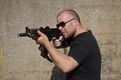picture of kalashnikov  - Man with glasses is holding Kalashnikov rifle - JPG