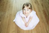 A Nice Little Girl Sit on the Floor with a Dress