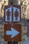 picture of outhouses  - Brown and white sign for public restrooms at a state park - JPG