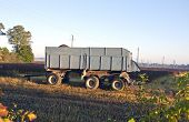 Tractor Trailer On Farm Field In Autumn Morning