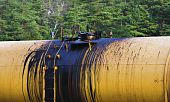 picture of nonrenewable  - oil leking from tank on railroad against tree background - JPG