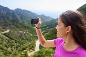 Girl taking smartphone picture of mountain nature. Female tourist traveling on road trip or hike in mountainous Anaga of Tenerife, Canary islands. Summer vacations.