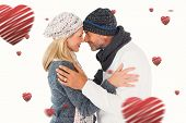 Happy couple in winter fashion embracing against hearts