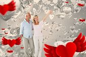 Smiling couple walking and pointing against grey valentines heart pattern
