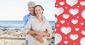 Happy casual couple hugging by the coast against heart pattern