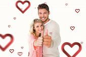 Attractive couple showing thumbs up to camera against hearts