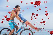 Man giving girlfriend a lift on his crossbar against red heart balloons floating