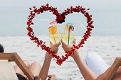 Couple clinking glasses of cocktail on beach against heart made of petals