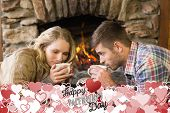 Romantic couple drinking tea in front of lit fireplace against happy valentines day