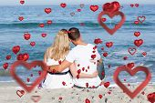 Affectionate couple sitting on the sand at the beach against love heart pattern