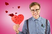 Geeky hipster holding a heart card against pink vignette