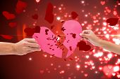 pic of broken hearted  - Hands holding two halves of broken heart against valentines heart design - JPG