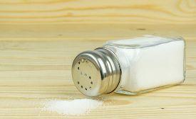 picture of salt shaker  - A glass salt shaker with metal lid and spilled salt - JPG