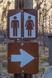 foto of outhouse  - Brown and white sign for public restrooms at a state park - JPG