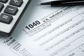 image of fill  - Filling income tax form with pen and calculator - JPG