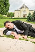 pic of unemployed people  - Frustrated unemployed man with sign lying down the lawn - JPG