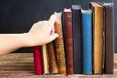 picture of vintage antique book  - Hand taking book from wooden bookshelf  with row of antique books - JPG