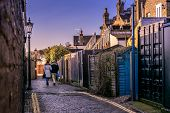 picture of cobblestone  - A couple walking down a cobblestone street in an old town - JPG
