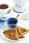 foto of crepes  - Homemade Crepes Folded In Triangles With Black Currant Jam And Cup Of Tea - JPG