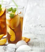 stock photo of iced-tea  - Peach Ice Tea in glass cup on wooden table - JPG