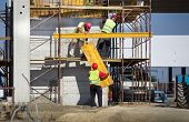 foto of scaffold  - Team work at construction site workers passing metal formworks on scaffolds - JPG