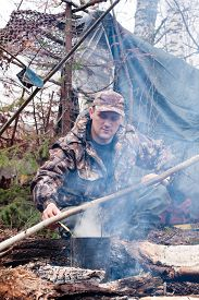foto of hunter  - the hunter cooking dinner over a campfire - JPG