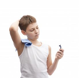 image of shoulder-blade  - Young boy in a sleeveless white shirt with a towel over his shoulder and and a shaving razor blade in his hand - JPG