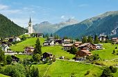 Village And Chapel In Swiss Alps