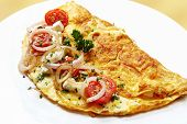 Omelette with cherry tomatoes, red onion, mozzarella, goat's cheese and herbs.  A delicious, nutritious breakfast.