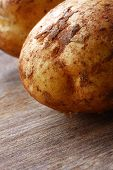 Unwashed potatoes on a wooden chopping board.  Shallow depth of field.
