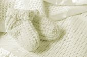 Baby booties on a soft baby blanket.  Soft and warm for the new arrival.
