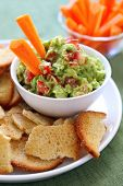 Avocado guacamole served with carrot sticks and bagel crisps - a healthy variation of this delicious