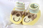stock photo of sock-monkey  - Cute baby booties with smiling monkey faces and ears - JPG